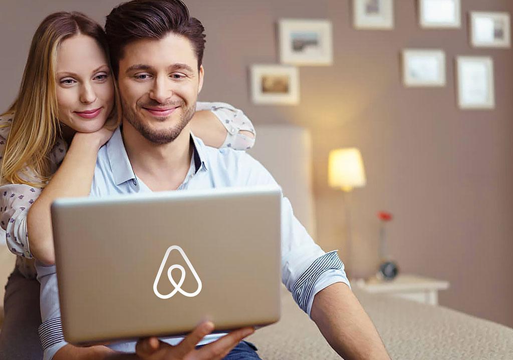фотография молодой пары с ноутбуком. На крышке ноутбука знаковый логотип Airbnb. Мужчина и Женщина смотрят в ноутбук и улыбаются. Фотоколлаж изображает пользователей сервиса краткосрочной аренды Аирбнб, которые хотят забронировать жилье и могут стать гостями начинающего хоста (хозяина)_