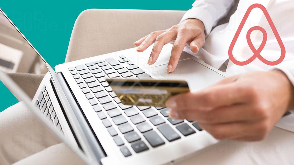 заставка статьи под названием: Как происходит оплата жилья на Airbnb - способы оплаты на Аирбнб. Изображение – коллаж с фотографией пользователя сервиса, который совершает бронирование на платформе. На коленях будущего гостя лежит ноутбук, палец правой руки скользит по тачпаду. В левой руке плательщик держит банковскую кредитную карту_