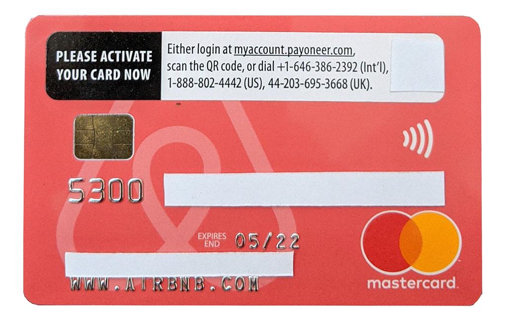 фотография карты Mastercard международной платежной системы Payoneer со знаковым логотипом Airbnb и закрытыми номером карты и ФИО владельца. Предоплаченная дебетовая карта Пейониар Мастеркард может быть заказана через сервис Аирбнб хозяином сдающегося жилья. Выплаты за прием гостей могут происходить с выводом денежных средств в валюте на счет этой карты_