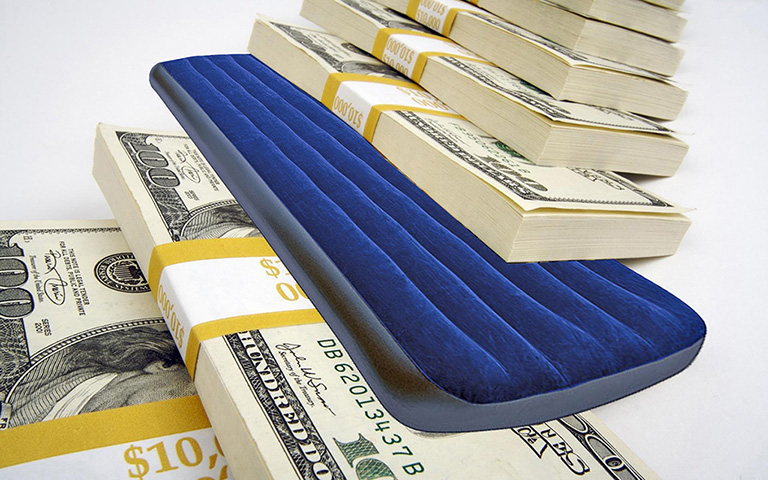 изображение коллаж: надувной матрас зажат между пачками долларов_