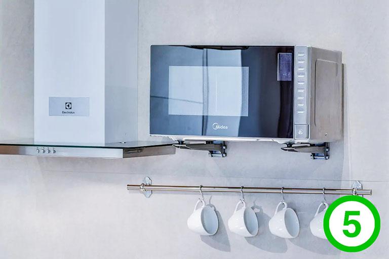 фото-изображение№5 – крупный план кадра на детали кухни с видом сильного приближения на удобства для гостя: микроволновая печь, кухонная вытяжка, чашки_