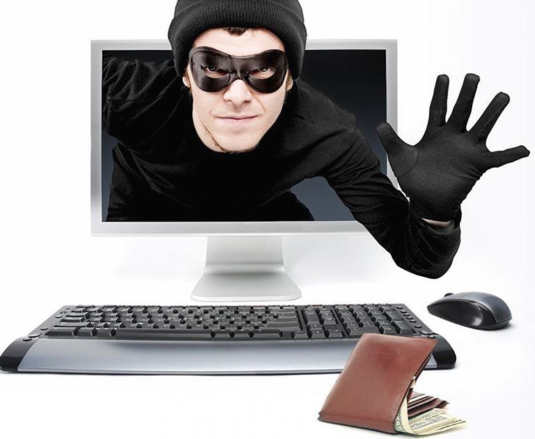 фото коллаж с человеком в маске, который вылезает из монитора и хватает кошелек на столе – обман через поддельную страницу в момент оплаты онлайн бронирования_