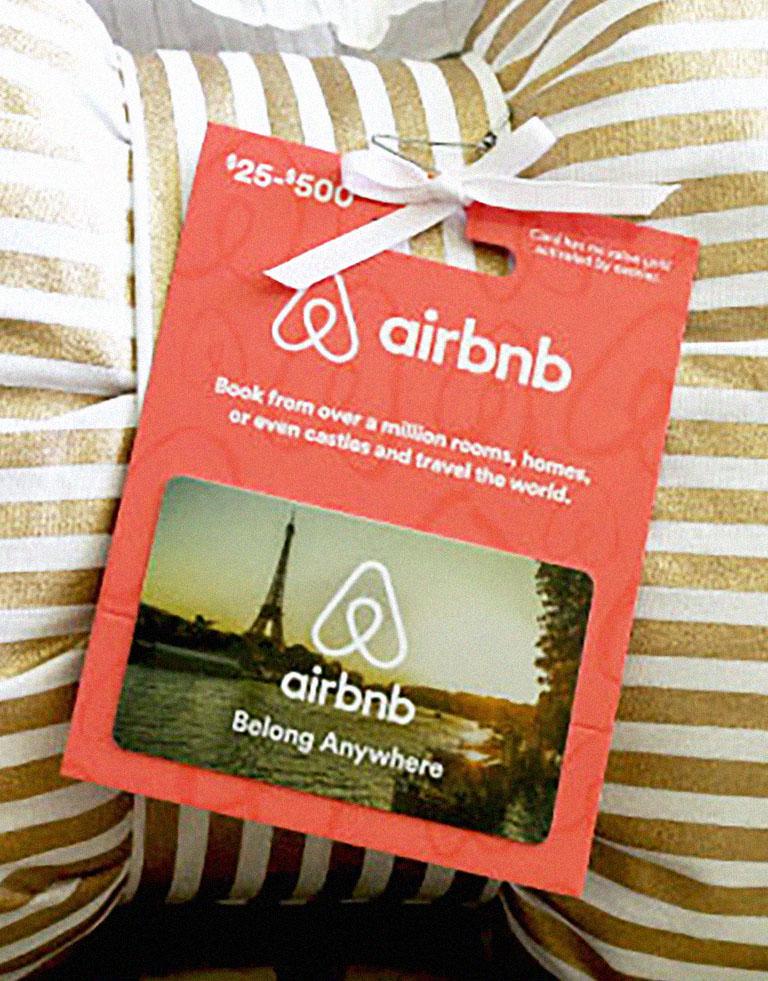 фотография индивидуальной подарочной карты airbnb на фоне подушки с бантиком_