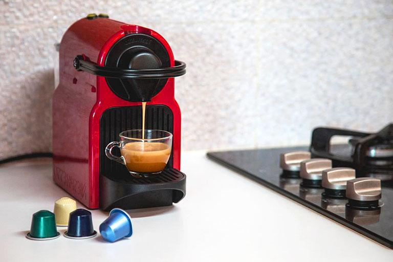 пример№10 сильного приближения кадра (детали) – капсульная кофе-машина с чашкой кофе и капсулами для гостей_