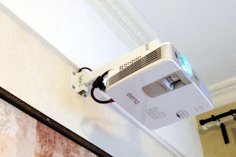 пример№9 крупного плана детали интерьера – видеопроектор на кронштейне под потолком для использования временными жильцами_