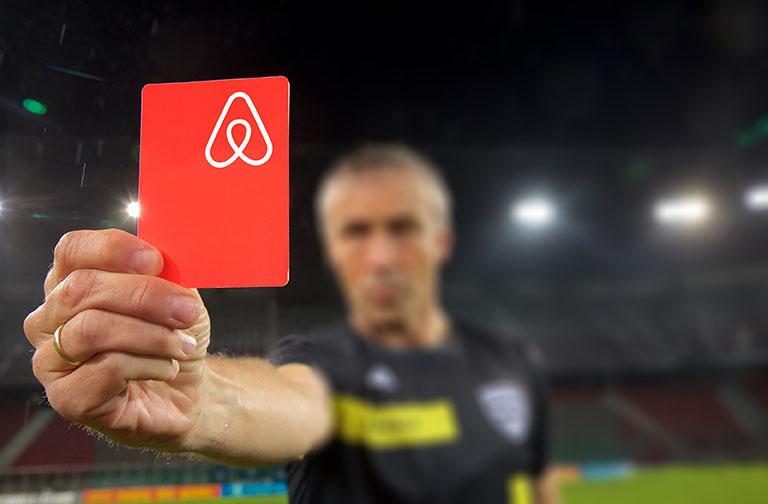 фотография коллаж: футбольный судья показывает красную карточку, на которой расположен знаковый логотип сервиса. Метафора штрафных санкций за нарушения_