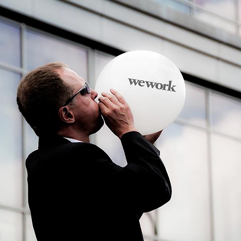 изображение-коллаж: фотография мужчины в деловом костюме и солнечных очках, надувающего воздушный шар. На шаре – пузыре расположен логотип компании, которая провалила выход на IPO. Метафора отражает неудачу убыточных стартапов при выходе на публичную биржу со своими акциями_