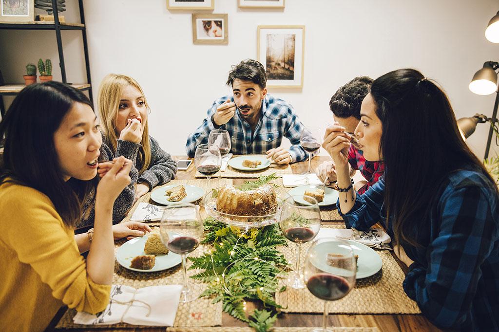 Символ знакомства, дружбы, общительности, и атмосферы теплого приема Airbnb – фотография компании друзей за столом, с вином и десертами_